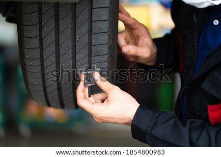 Mechanic checking checking the depth of car tire tread.  Car maintenance and auto service garage concept. Foto stock ©