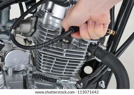 mechanic checking the spark plug lead on a motorcycle