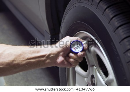 Mechanic checking tire pressure for increased gas mileage