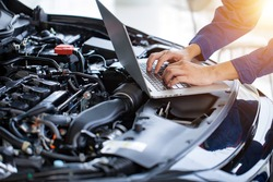 Mechanic checks the car engine with electronic tools. Modifying the engine with a computer Check service