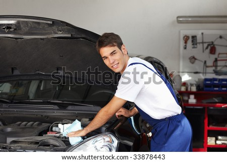 mechanic cleaning car engine and looking at camera