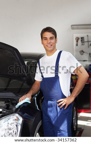 mechanic cleaning car engine and looking at camera. Copy space