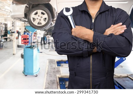 Mechanic cross arm holding wrench for maintaining car on lift at the repair shop