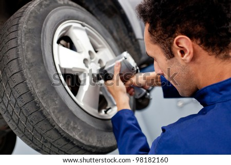 Mechanic fixing a puncture on a car at the garage