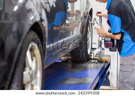 Mechanic fixing the wheel alignment device onto a car wheel. Focus is on the car wheel and wheel alignment device. #242399308