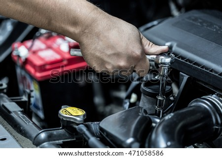 Mechanic hand checking and fixing a broken car in car service garage #471058586