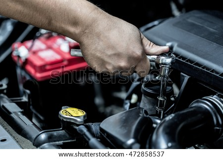 Mechanic hand checking and fixing a broken car in car service garage #472858537