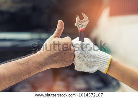 Mechanic hand checking and fixing a broken car in  garage.hand of mechanic with thumbs up and tool