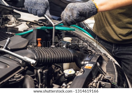 Mechanic hands working holding a wrench and socket on the engine in car at garage .car maintenance and service and repair concept.selective focus. selective focus #1314619166