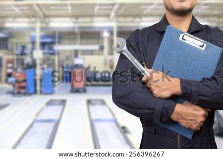 mechanic holding a clipboard of service order with wrench at the repair shop