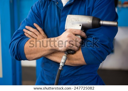 Mechanic holding a drill tool at the repair garage