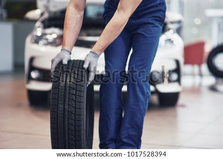Mechanic holding a tire tire at the repair garage. replacement of winter and summer tires. #1017528394