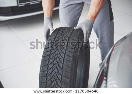 Mechanic holding a tire tire at the repair garage. replacement of winter and summer tires. #1178584648
