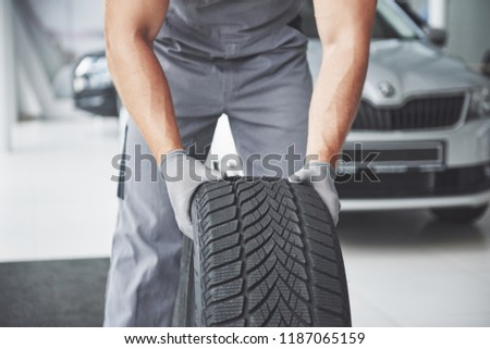 Mechanic holding a tire tire at the repair garage. replacement of winter and summer tires. #1187065159