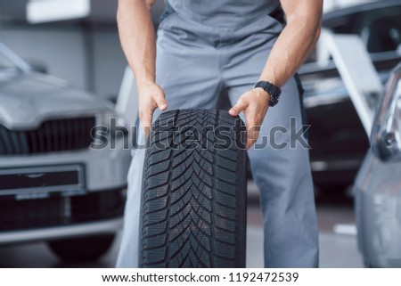 Mechanic holding a tire tire at the repair garage. replacement of winter and summer tires. #1192472539