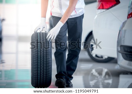 Mechanic holding a tire tire at the repair garage. replacement of winter and summer tires.  #1195049791