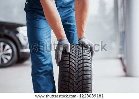 Mechanic holding a tire tire at the repair garage. replacement of winter and summer tires. #1228089181