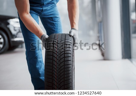 Mechanic holding a tire tire at the repair garage. replacement of winter and summer tires. #1234527640