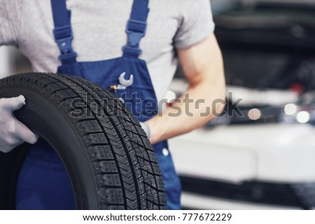 Mechanic holding a tire tire at the repair garage. replacement of winter and summer tires. #777672229