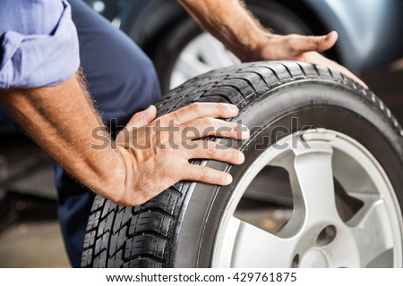 Mechanic Holding Car Tire At Garage #429761875