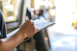 Mechanic holding clipboard with checking truck in service center,Preforming a pre-trip inspection on a truck,preventive maintenance,spot focus