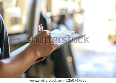 Mechanic holding clipboard with checking truck in service center,Preforming a pre-trip inspection on a truck,preventive maintenance,spot focus Imagine de stoc ©