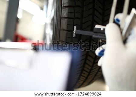 Mechanic holding tool hand that measures tire wear. Wheel balancing. Trust tire center to replace wheels. Pre-trial settlement damage after car accident. Tire fitting and balancing equipment Imagine de stoc ©