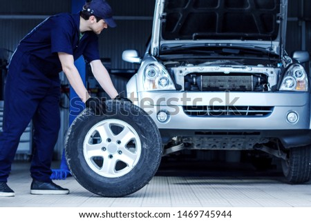 Mechanic in blue jumpsuit is repairing car at modern service station. Repairman is rolling wheel on floor of workshop auto repair shop. Silver vehicle on background. Tire fitting concept.