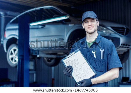 Mechanic in blue jumpsuit is repairing car at service station garage. Smiling repairman is holding job sheet for repairs of vehicle in workshop. Silver automobile on hydraulic lift on background.