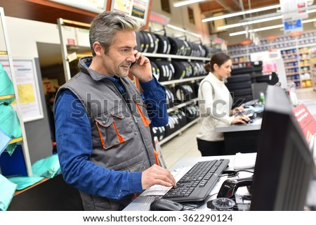 Mechanic in car repair shop talking on phone