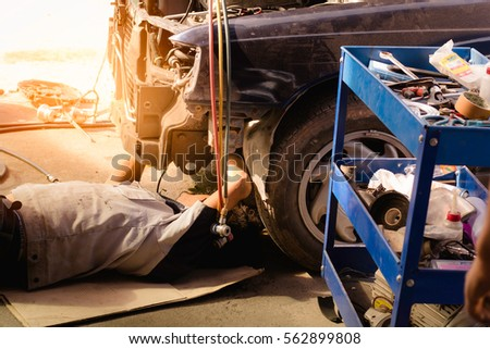 mechanic in uniform lying down...