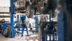 Mechanic inspecting car suspension detail and wheel car of lifted automobile at repair service station. Car service station. Preventive maintenance.