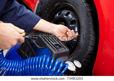 Mechanic inspecting the tire pressure in auto repair shop.