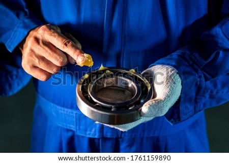 Mechanic is putting lubricant grease into ball bearing in the industrial factory, Technician Industrial Concept Сток-фото ©