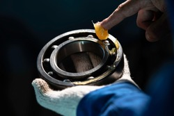 Mechanic is putting yellow grease in the into bearing, engineering and industrial concept