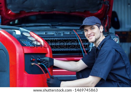 Mechanic is repairing car at service station. Repairer in jumpsuit is conducting diagnostics. Vehicle is connected to equipment for maintenance and refueling of air conditioners in auto repair shop.