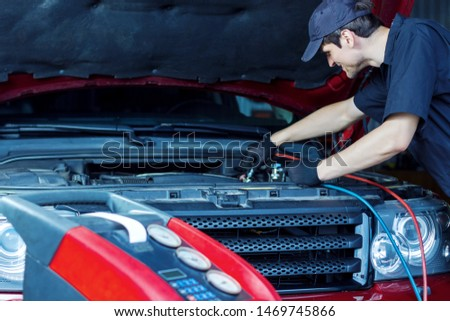 Mechanic is repairing car at service station. Repairer in jumpsuit is conducting diagnostics. Vehicle is connected to equipment for maintenance and refueling of air conditioners in auto repair shop. #1469745866