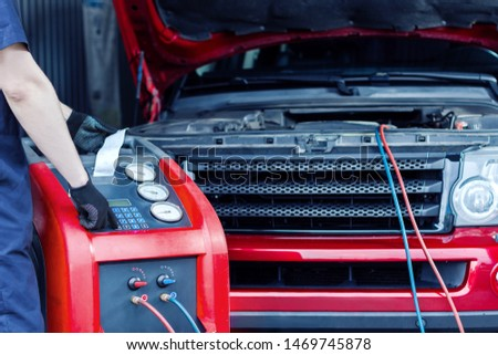 Mechanic is repairing car at service station. Repairer in jumpsuit is conducting diagnostics. Vehicle is connected to equipment for maintenance and refueling of air conditioners in auto repair shop. #1469745878