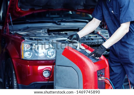 Mechanic is repairing car at service station. Repairer in jumpsuit is conducting diagnostics. Vehicle is connected to equipment for maintenance and refueling of air conditioners in auto repair shop. #1469745890