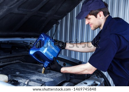 Mechanic is repairing, conducting diagnostics of car at service station. Repairer is holding blue canister and filling fueling engine oil in motor. Vehicle in workshop auto repair shop.