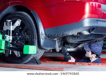 Mechanic is repairing red car at service station. Repairer in blue jumpsuit and cap is tightening nut. Vehicle on stand with sensors on wheels for alignment camber check in auto repair shop.