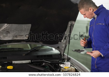 Mechanic looking at a car engine while holding a clipboard in a garage