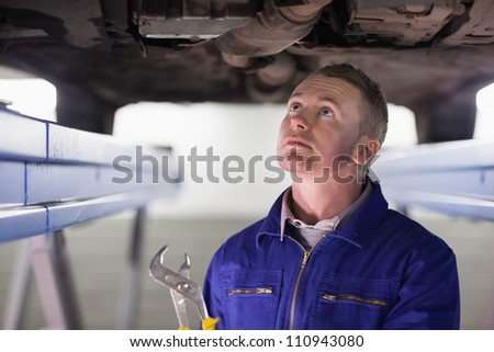 Mechanic looking at the below of a car while holding an adjustable pliers in a garage