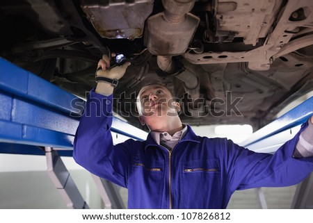 Mechanic looking the below of a car while holding a flashlight in a garage