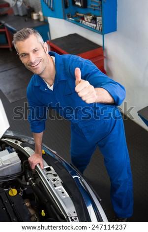 Mechanic looking up at camera at the repair garage #247114237