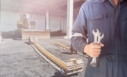 Mechanic man hold  spanner tool for industrial maintenance and repair bulldozer in power plant
