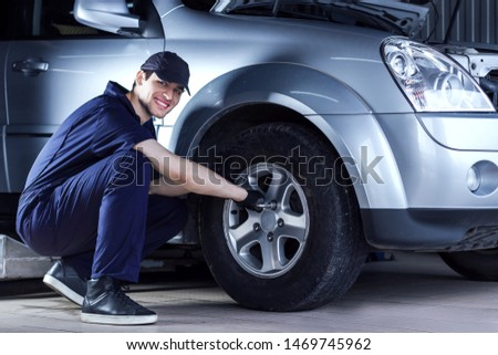 Mechanic man in blue jumpsuit is repairing car at service station garage. Repairman is unscrewing nuts on disk with wrench to remove wheel at workshop auto repair shop.Tire fitting concept.