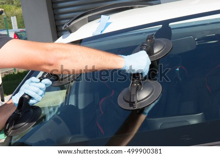 Mechanic man is changing windscrenn on a car #499900381