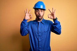 Mechanic man with beard wearing blue uniform and safety helmet over yellow background looking surprised and shocked doing ok approval symbol with fingers. Crazy expression