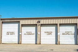 Mechanic on Duty, Wheel Alignment, Service Department, state inspection, a tan metal building with white roll-up doors, located in South Louisiana.